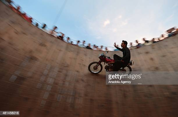 A performer rides a motorbike on the Wall of Death at Nawaz Sharif Park in Rawalpindi Pakistan on July 20 2015