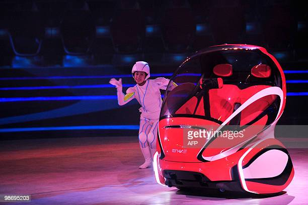 A performer shows off a futuristic electric car seat which changes angle according to the speed of the vehicle on display in the Shanghai Automotive...