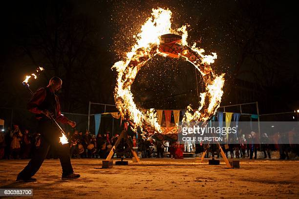 A performer spins a burning baton during the 27th Annual Kensington Market Winter Solstice Parade in Toronto on December 21 2016 / AFP / Cole Burston