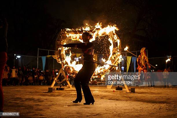 A performer spins a burning hula hoop as she takes part in the 27th Annual Kensington Market Winter Solstice Parade in Toronto on December 21 2016 /...