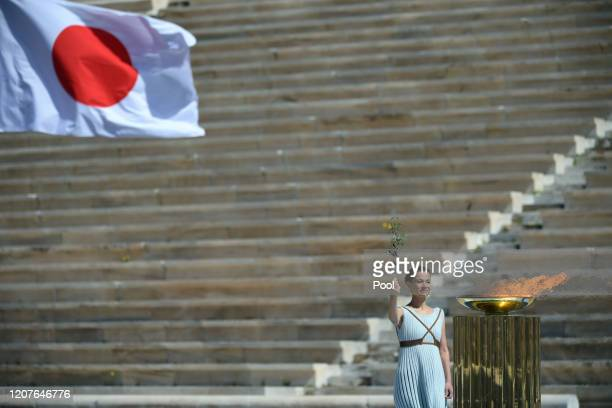 A performer stands alongside the Olympic flame the olympic torch during the Flame Handover Ceremony for the Tokyo 2020 Summer Olympics on March 19...