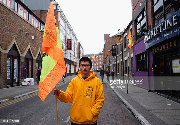 A performer stands with his flag at the start of the day as the Chinese community come together to welcome in the Chinese New Year on February 22...
