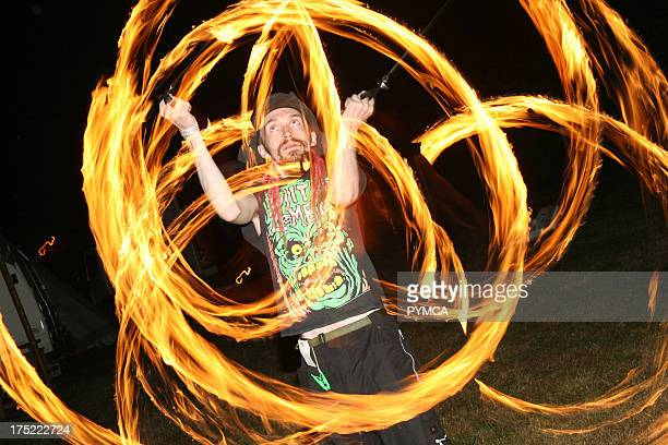A performer swinging fire Poi Poi at the Workhouse Festival Wales 2006
