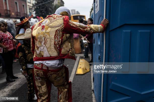 A performer takes a break during the Day of the Dead parade on Paseo de la Reforma Avenue on November 2 2019 in Mexico City Mexico Observants...