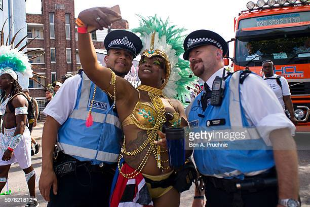 A performer takes a selfie with two police officers during the Notting Hill Carnival on August 29 2016 in London England The Notting Hill Carnival...