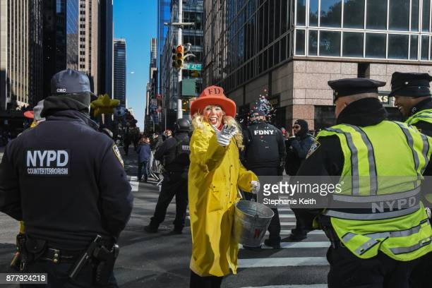 A performer throws confetti near law enforcement on 6th Ave amid increased security during the annual Macy's Thanksgiving Day parade on November 23...