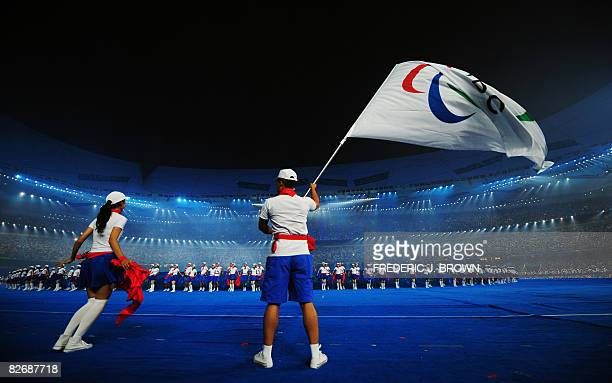 Performer waves the International Paralympic Committee flag as the 2008 Beijing Paralympic Games opening ceremony kicks off at the National Stadium,...