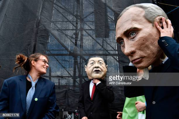 A performer wearing a mask of Russian President Vladimir Putin takes it off during a demonstration called by several NGOs ahead of the G20 summit in...