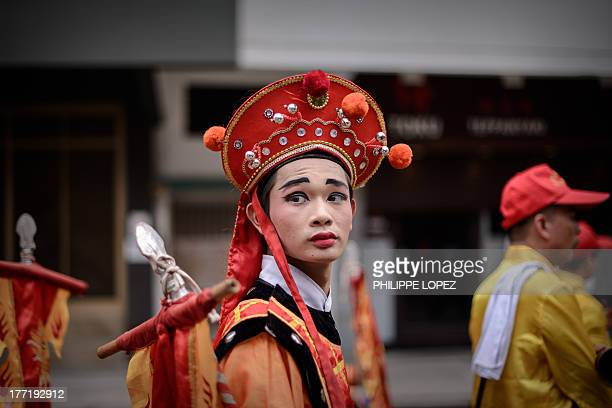 Performer wearing a traditional costume takes part in a parade for the Hungry Ghost Festival in Hong Kong on August 22, 2013. The festival,...