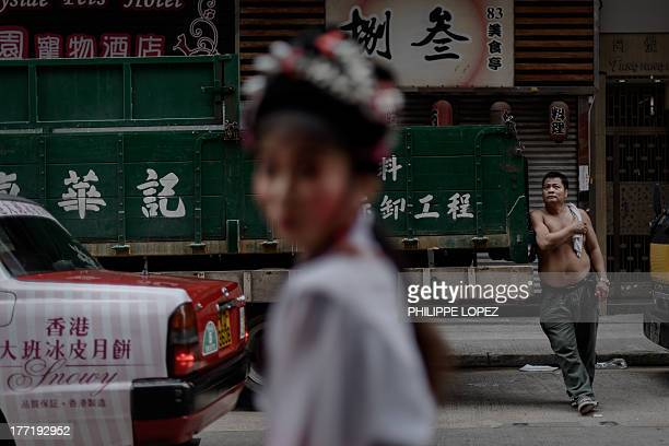 Performer wearing a traditional costume walks past a man standing by a truck during a parade for the Hungry Ghost Festival in Hong Kong on August 22,...