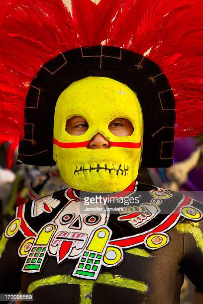 CONTENT] Performer wearing Aztec costume with skeleton mask at the Dia de los Muertos Parade Milwaukee WI
