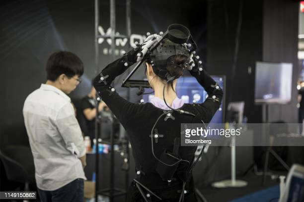 A performer wears a motion capture suit at the booth of Xmov Konjac a unit of Konjac Information Technolgy Co during the CES Asia Show in Shanghai...