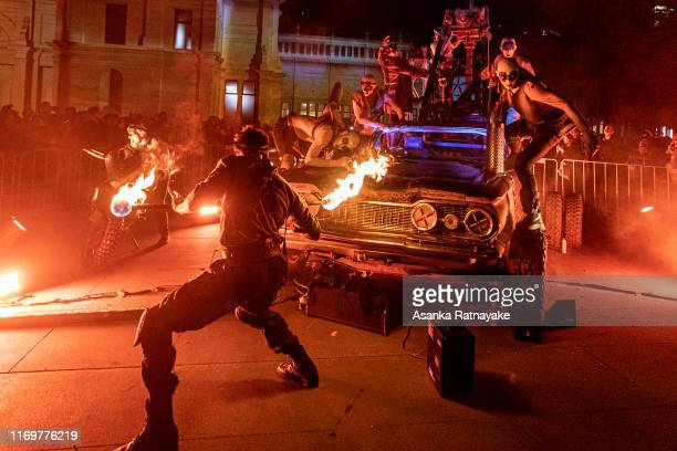 Performers a part of the Mad Max: Fury Road live performance as a fire twirler twist a baton during White Night Melbourne Reimagined on August 23,...