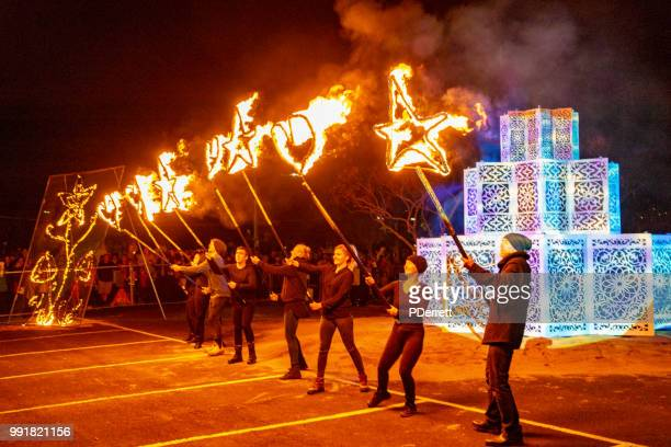 performers about to light a bonfire engage in some fire and flare twirling. - winter solstice stock pictures, royalty-free photos & images