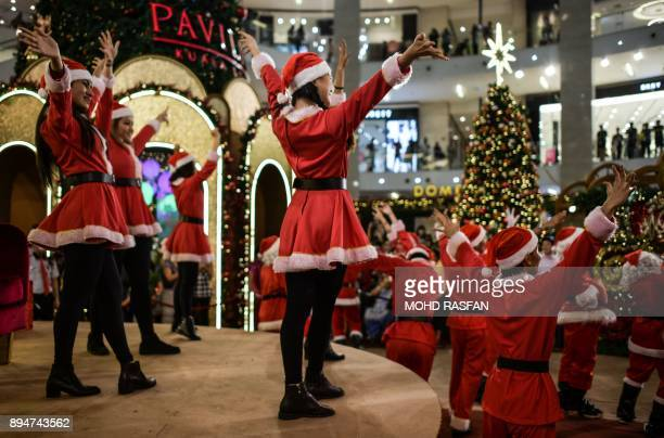 Performers clad in holidaythemed outfits dance at a shopping mall in Kuala Lumpur on December 18 2017 Every year as Christmas approaches shopping...