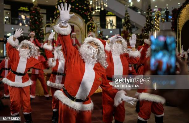 Performers clad in Santa Claus outfits dance at a shopping mall in Kuala Lumpur on December 18 2017 Every year as Christmas approaches shopping malls...
