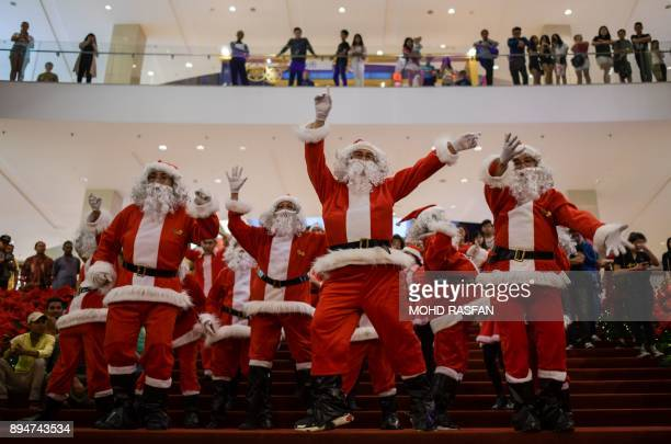 TOPSHOT Performers clad in Santa Claus outfits dance at a shopping mall in Kuala Lumpur on December 18 2017 Every year as Christmas approaches...