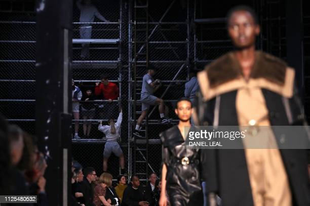 Performers climb the back wall during the British fashion house Burberry 2019 Autumn / Winter collection catwalk show at London Fashion Week in...