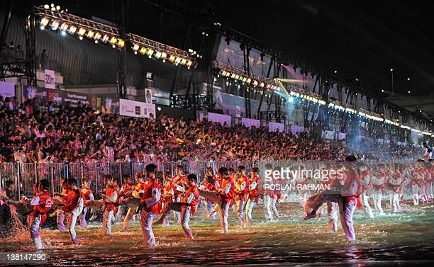 Performers dance down a specially constructed 360 metre waterway during the annual Chinese New Year Chingay parade to mark the year of the dragon in...