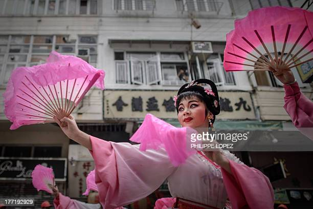 Performers dance during a parade for the Hungry Ghost Festival in Hong Kong on August 22, 2013. The festival, celebrated in the seventh lunar month...