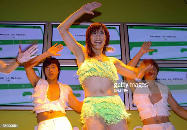 Performers dance in front of the monitiors during the Computex Taipei at the World Trade Center 31 May 2005. Some 2,828 booths from 1,347 cmpanies...