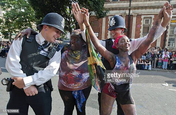 Performers dance with police officers on the first day of the Notting Hill Carnival in west London on August 25 2013 Running over two days the...