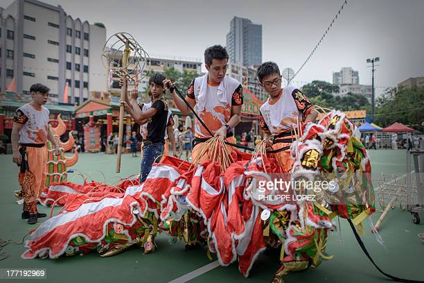 Performers dismantle a dragon at the end of a parade for the Hungry Ghost Festival in Hong Kong on August 22 2013 The festival celebrated in the...