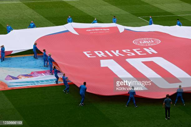Performers display a banner depicting the jersey of Denmark's midfielder Christian Eriksen who suffered a cardiac arrest during a group stage match...