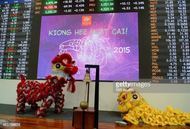Performers donning lion dance costumes perform next to the electronic display at the Philippine stock exchange during Lunar New Year of the Sheep...