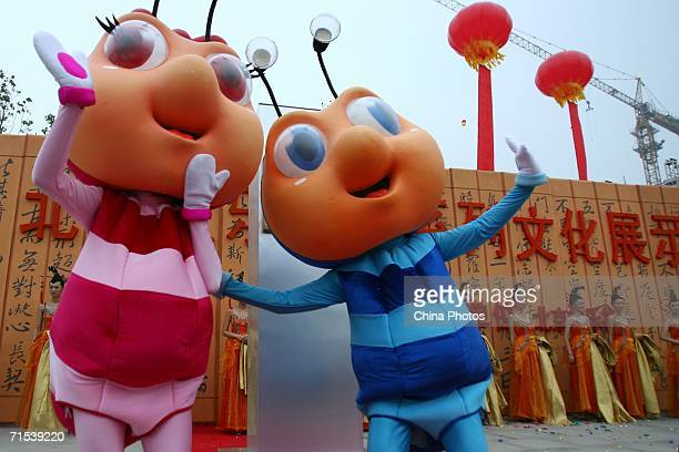 Performers dressed as cartoon figures welcome customers during a ceremony to mark the official opening of Chinese Theme Park 'Happy Valley' on July...