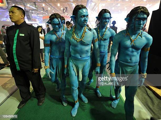 Performers dressed as characters of Hollywood awardwinning director James Cameron's film 'Avatar' walk past a visitor prior to a performance during...
