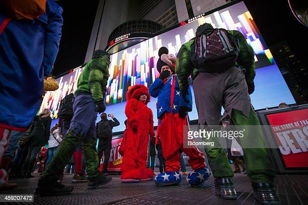 Performers dressed as Marvel's Incredible Hulk second left and right Sesame Street's Elmo center and Walt Disney Co's Mickey Mouse second right...