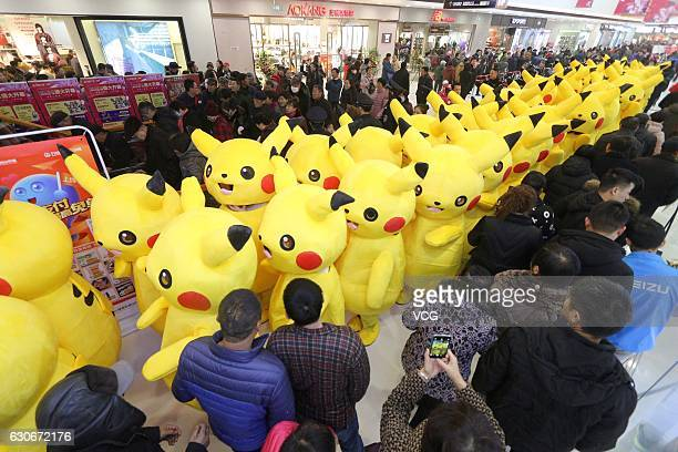 Performers dressed as mascot Pikachu take part in a parade at the opening ceremony of a shopping mall on December 30 2016 in Binzhou Shandong...