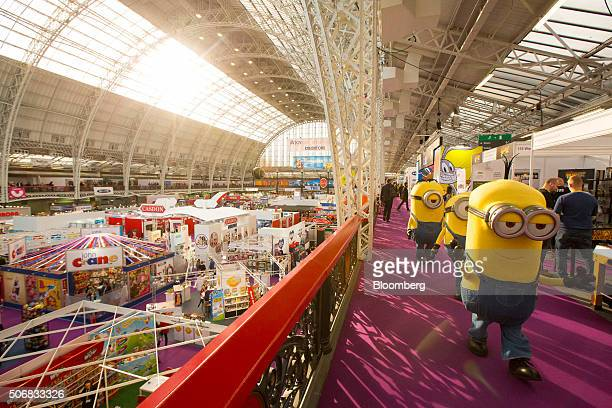 Performers dressed as Minions characters from the Universal Pictures movie of the same name walk through the main hall at the British Toy And Hobby...