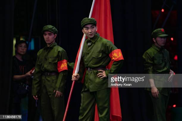 Performers dressed as People's Liberation Army soldiers gather in backstage during a rehearsal of a Cantonese opera Trump on Show on April 11 2019 in...