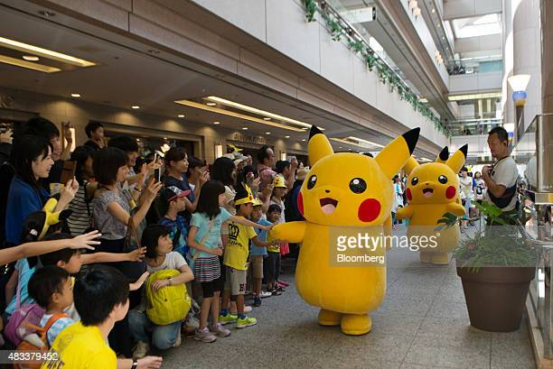 Performers dressed as Pikachu a character from Nintendo Co's Pokemon game title interact with children as they march through a shopping mall during...