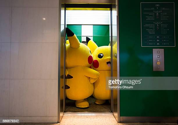 Performers dressed as Pikachu a character from Pokemon series game titles ride on an elevator during the Pikachu Outbreak event hosted by The Pokemon...