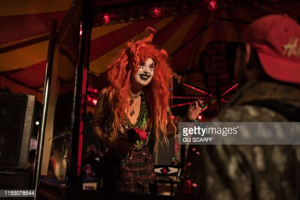 Performers entertain festival-goers in the Unfairground in the Shangri-La area of the Glastonbury Festival of Music and Performing Arts on Worthy...