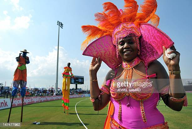 Performers from a local carnival band walk on the field during the first T20 match between West Indies and New Zealand at the Central Broward...