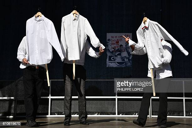 Performers from a small theater company hold shirts as they perform an act on a makeshift stage set up near the Bobigny courthouse northeast of Paris...