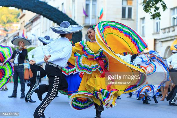Performers from Mexican group in traditional costumes dancing on street