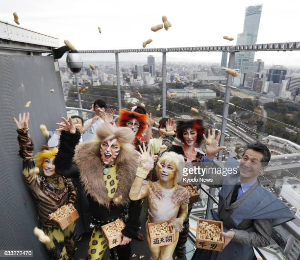 Performers from Shiki Theater Company's Cats production scatter roasted soybeans to drive demons away at the observatory of Tsutenkaku tower in the...