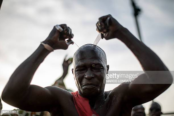 Performers from the Joles ethnic group in Gambia prepare to perform with sharp blades which they say will demonstrate the magic powers of a spiritual...