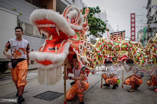 Performers hold a dragon during a parade for the Hungry Ghost Festival in Hong Kong on August 22 2013 The festival celebrated in the seventh lunar...