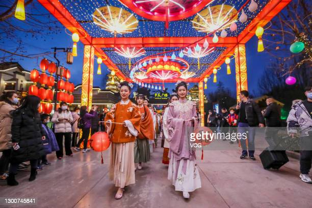 Performers in Han costumes holding festive lanterns written with Chinese character 'Fu', meaning good fortune, parade at a tourist attraction before...