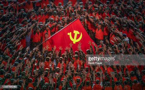 Performers in the costume of emergency workers surround a large Communist Party flag during a mass gala marking the 100th anniversary of the...