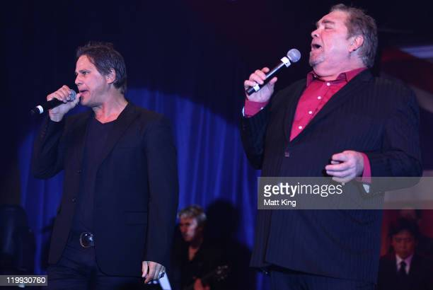 Performers Jon Stevens and Doug Parkinson sing on stage during the Australian Olympic Committee Black Tie Dinner at the Sydney Convention Exhibition...
