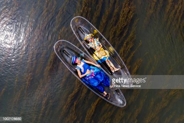 Performers lie on transparent boats as they rehearse for a show on the Lijiang River on July 15 2018 in Guilin Guangxi Zhuang Autonomous Region of...