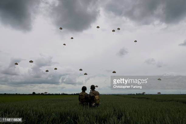 Performers look on as 280 paratroopers take part in a parachute drop onto fields at Sannerville on June 05 2019 at Sannerville France Veterans...