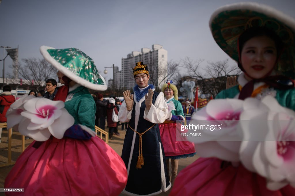 TOPSHOT - Performers make their way through the Olympic plaza of the coastal cluster venues for the 2018 Pyeongchang Winter Olympic games, in Gangneung on February 19, 2018. / AFP PHOTO / Ed JONES